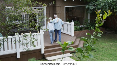 Senior couple walking into the house together