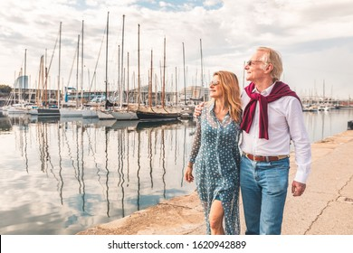 Senior couple walking near the port in Barcelona - Adult woman and man embracing and enjoying time together on a sunny day in Spain - Summer and travel concepts at seaside in Barcelona