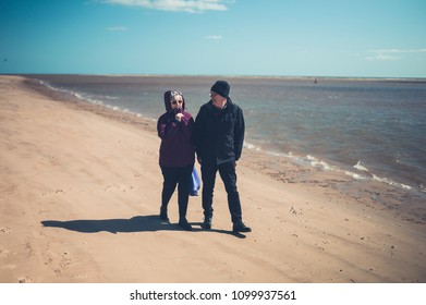 A senior couple walking on the beach and enjoying retirement