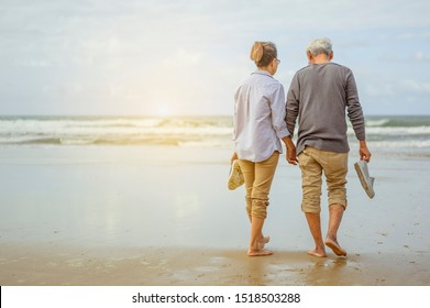 Senior couple walking on the beach holding hands at sunrise, plan life insurance at retirement concept.