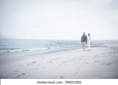 Senior couple walking on the beach on a sunny day