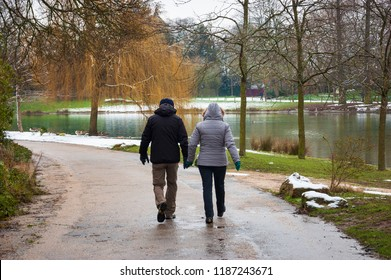 Senior couple walking in park near Daumesnil lake (Paris, France) on wet road in rare snowy day.