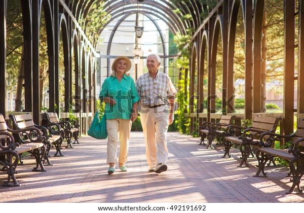 Senior Paar laufen und lächeln. Leute in Parkanlagen. Wunderbarer Tag für einen Spaziergang. Wertvolle Momente des Lebens.