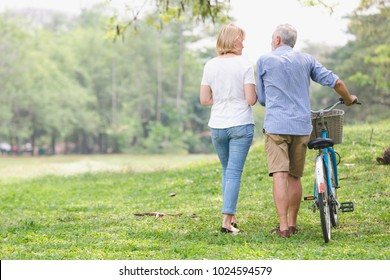 Senior couple walking their bike along happily talking happily.