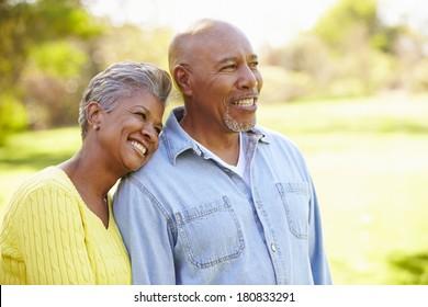 Senior Couple Walking Through Autumn Woodland