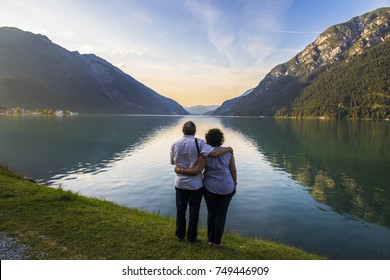 Senior couple watching sunset at Lake Achen (Achensee), a lake north of Jenbach in Tyrol, Austria