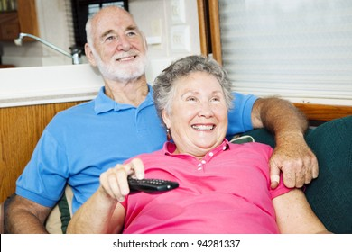 Senior couple watching television in their small traveling motor home.