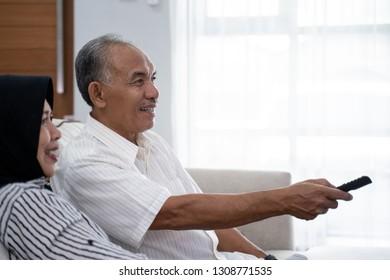 senior couple watching tv sitting side a grandma on sofa