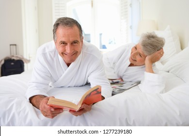 Senior couple wearing bathrobes lying on bed smiling as man reads book