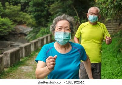 Seniorenpaar mit Gesichtsmaske und Spaziergang durch den Naturpark