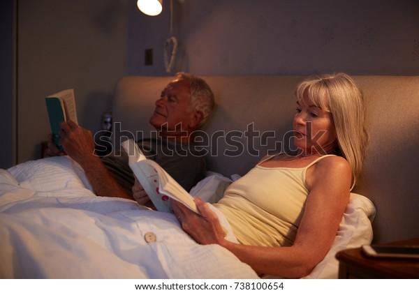 Senior Couple Wearing Pajamas Lying In Bed Reading