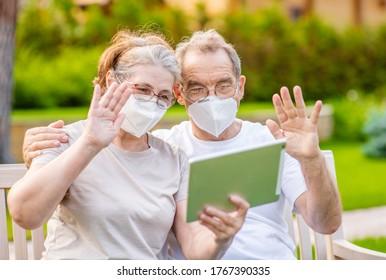 Hochrangiges Paar mit Schutzmaske, das während der Epidemie des Coronavirus auf dem Tablet-Computer einen Videochat führt