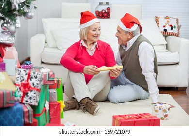 Senior couple wearing Santa hats looking at each other during Christmas at home