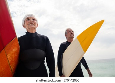 Senior couple in wetsuit holding surfboard on beach on a sunny day
