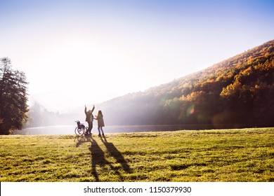 Senior couple with wheelchair in an autumn nature.