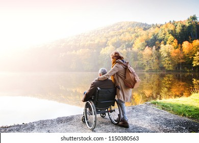 Senior couple with wheelchair in autumn nature.