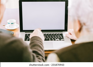 Senior couple working with Laptop, focus on screen
