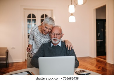 A senior couple working on a laptop and checking their finances.