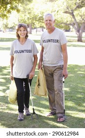 Senior Couple Working As Part Of Volunteer Group Clearing Litter In Park