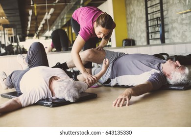 Senior couple workout in rehabilitation center. Personal trainer helps elderly couple to do stretching on the floor.