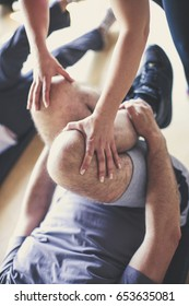 Senior couple workout in rehabilitation center. Personal trainer helps elderly couple to do stretching on the floor. Only legs.