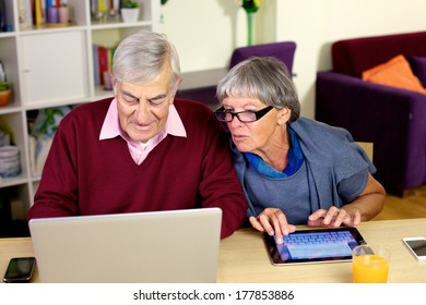 Senior couple writing emails on their notebook computer and tablet.