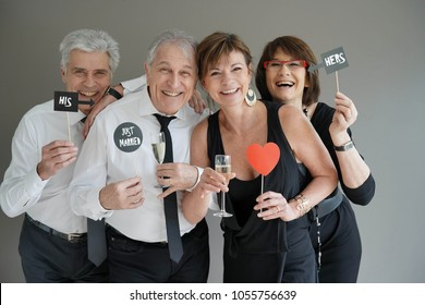 Senior couples celebrating wedding and using photo props