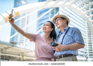 Senior couples who smile happily are taking selfies with a smartphone.