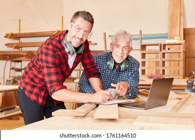 Senior craftsman and colleague work as a team in carpentry or joinery