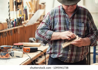Senior craftsman grinding wooden part with sandpaper grinder machine at carpentry workshop. Mature master polishing details of craft object. DIY home workplace