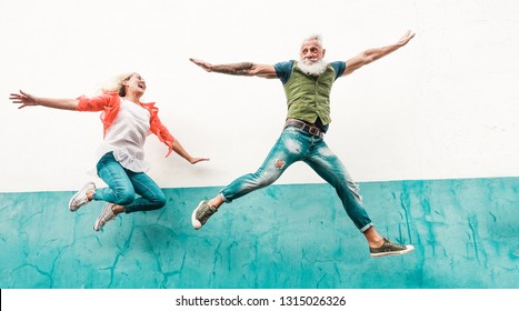 Senior crazy couple jumping outdoor - Mature people having fun dancing and celebrating outside - Joyful elderly lifestyle concept - Focus on faces