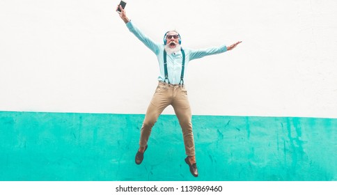 Senior crazy man jumping and listening music outdoor - Happy mature male celebrating and dancing outside - Joyful elderly lifestyle concept - Focus on him