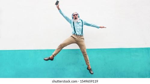 Senior verrückte Mann springen und hören Musik im Freien - Frohes reife männliche Feiern und Tanzen draußen - Fröhliches altes Lifestyle-Konzept - Fokus auf sein Gesicht