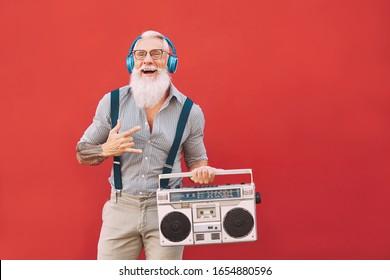 Homme fou expérimenté écoutant de la musique avec des écouteurs et une boombox vintage en plein air - Homme Hipster s'amusant à vivre dans le passé - Personnes âgées activité de vie - arrière-plan Rouge