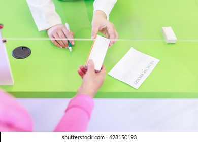 Senior customer in pharmacy buying and taking a box of medication Close up Overhead