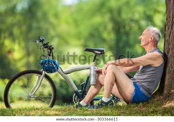 Senior cyclist sitting by a tree in a park with a water bottle in his hand and listening to music on headphones