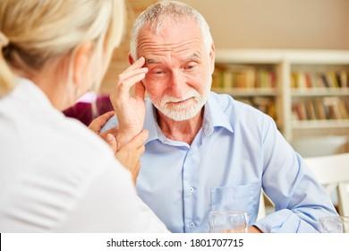 Senior bei Demenz oder Alzheimer ist trökomformiert durch Betreuerinnen Arzt