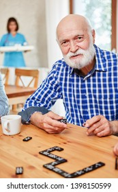 Senior with dementia or Alzheimer's playing in retirement home at domino