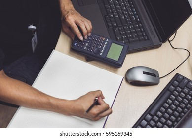 Senior design engineer calculating about engineering and take note in selective focus. calculator, laptop, monitor on working desk. man hard working.
