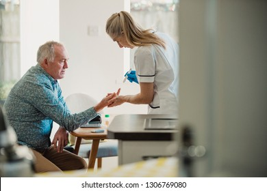 Senior diabetic man is having a check up at home from a district nurse. She is checking his blood glucose levels.
