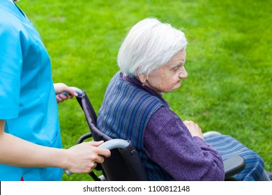 Senior disabled woman in wheelchair walking outdoor with female caretaker