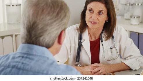 Senior doctor advising elderly patient