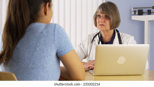 Senior doctor advising Mexican woman patient