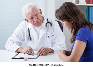 Senior doctor asking his young patient about medical history