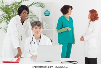 Senior doctor with colleagues in the office.