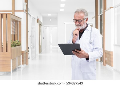 Senior doctor was examine a medical record in the hospital hallway
