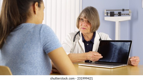 Senior doctor explaining neck x-ray to Mexican woman patient