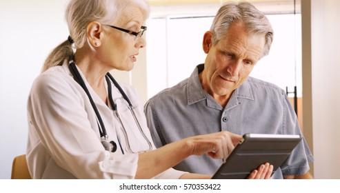 Senior doctor expressing health concerns with elderly man patient