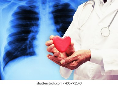 senior doctor hand hold heart with x ray film blur background , hospital care healthy concept