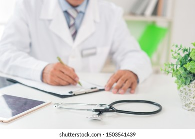 Senior doctor at his office in hospital working close-up prescription